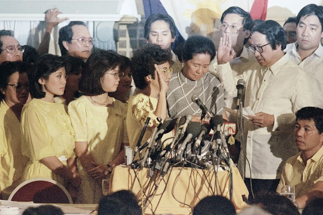 Corazon Aquino is taking the oath as the new president of the Philippines, Feb. 25, 1986. Others are unidentified.