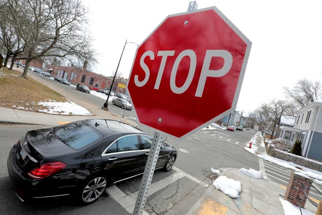 A motor vehicle stops at the newly installed stop signs on Cottage Street at the intersection with Elm Street in New Bedford.