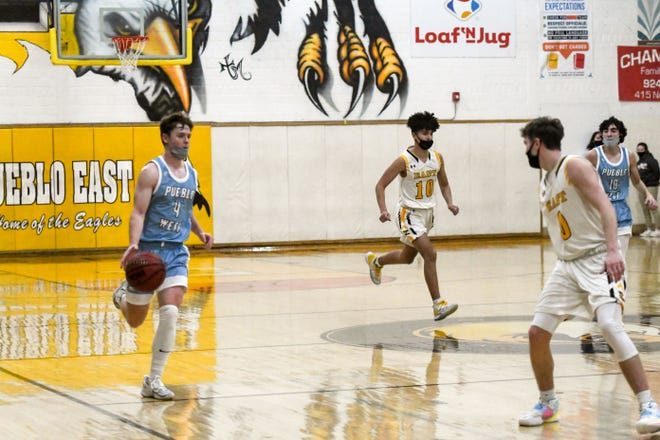 Pueblo West's Danny Spence, left, dribbles the ball up the court against Pueblo East on Thursday, Feb. 18, 2021, at Mel Spence Gym.