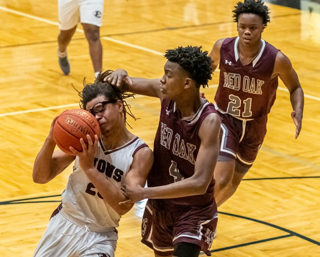 Red Oak's Reginald Osborne (4) fouls Ennis' Grant Gilmore (23) during Saturday's District 14-5A play-in game in Italy. The Hawks won in overtime, 51-50, to secure the No. 4 seed.