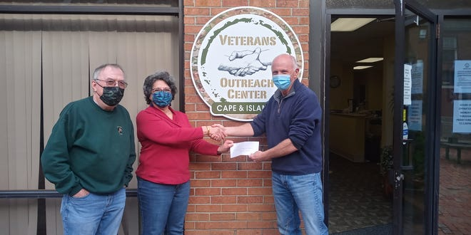 Judy Wilchynski, center, president of the Dennis-Yarmouth Women's Club, presents a donation check to Joe Taylor, right, Cape and Islands Veterans Outreach Center executive director, and VOC Treasurer William Blaisdell.
