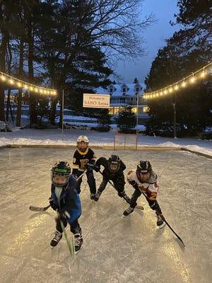 Front row, left ot right, Cal Wiggin, Frank French, Jack Wiggin, James Sabo playing in a backyard ice skating rink on Spring Valley Road made by Dante Muzzioli.
