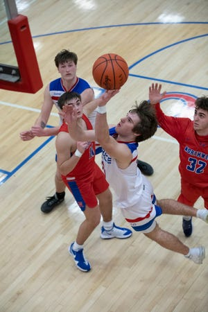 Junior Ben Nichols flies through the air as he attempts to score for Zane Trace during a Division III boys sectional semifinal game in Chillicothe, Ohio, on Feb. 22, 2021. Zane Trace defeated McDermott 58-47.