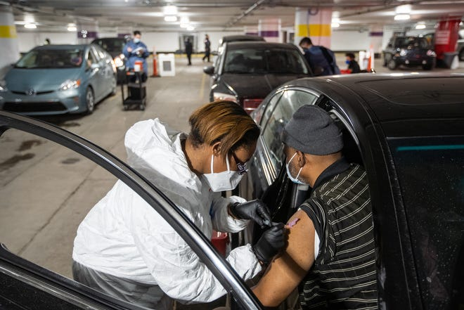 Malcolm Barnes of Detroit gets his first shot of the Moderna COVID-19 vaccine in an underground parking garage at TCF Center in downtown Detroit on Wednesday, February 3, 2021 as part of a drive-up distribution for the city of Detroit.