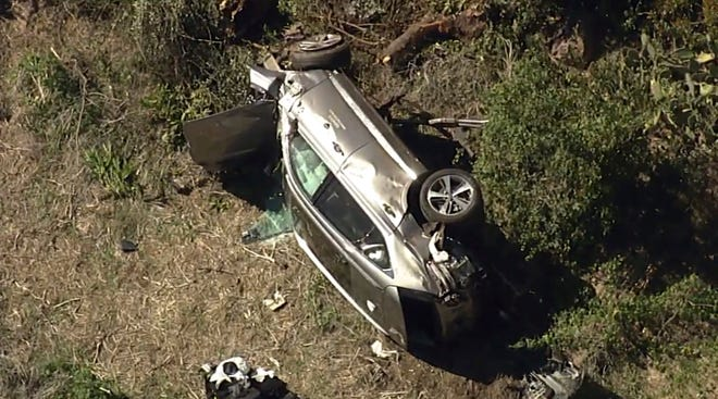 In this aerial image take from video provided by KABC-TV video, a vehicle rest on its side after a rollover accident involving golfer Tiger Woods along a road in the Rancho Palos Verdes section of Los Angeles on Tuesday.