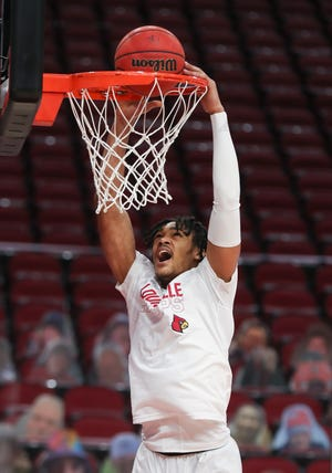Louisville's Dre Davis (14) dunks while warming up before their game against Notre Dame at the KFC Yum! Center in Louisville, Ky. on Feb. 23, 2021.