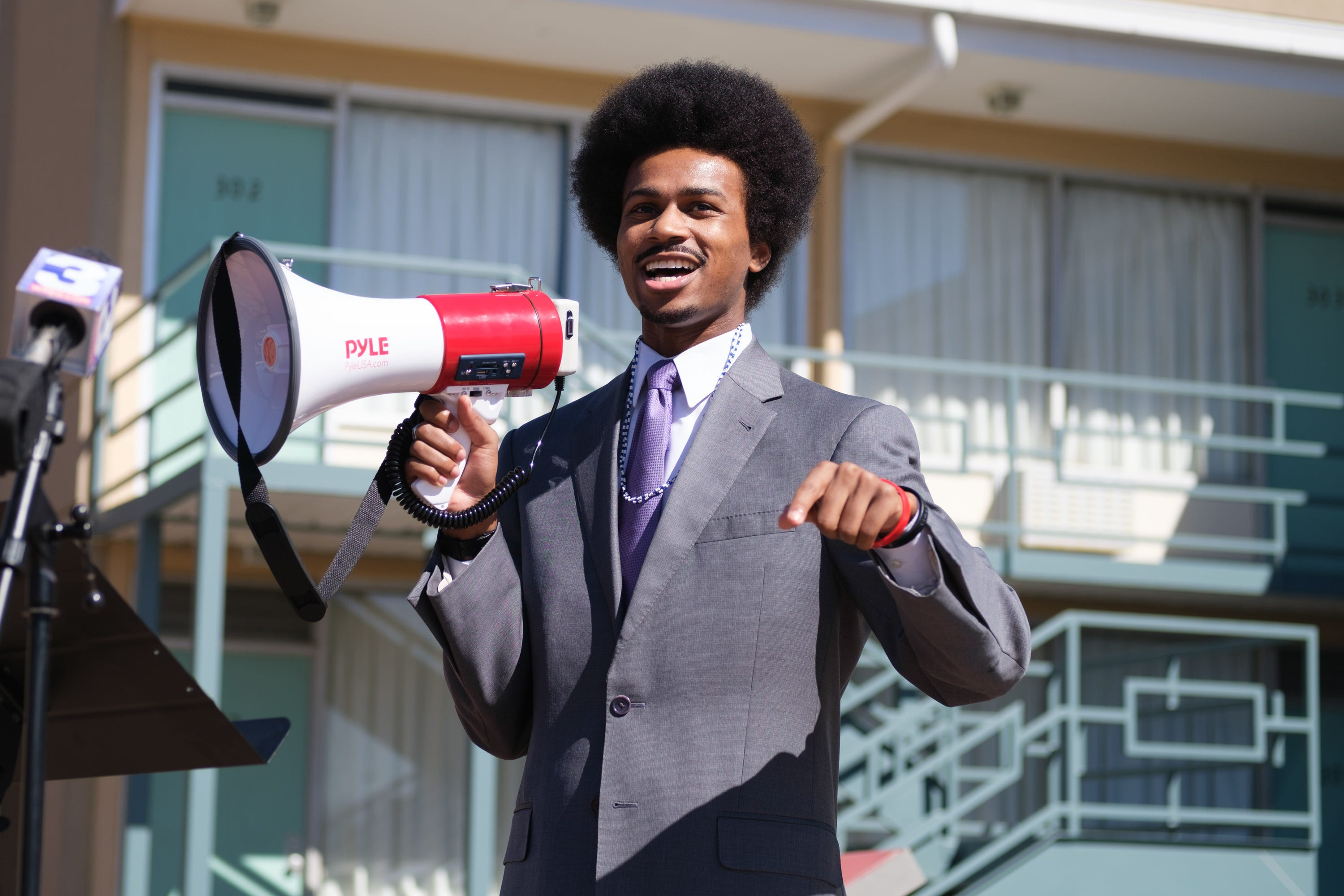 Justin Pearson in a gray suit stands in front of the National Civil Rights Museum holding a red megaphone.
