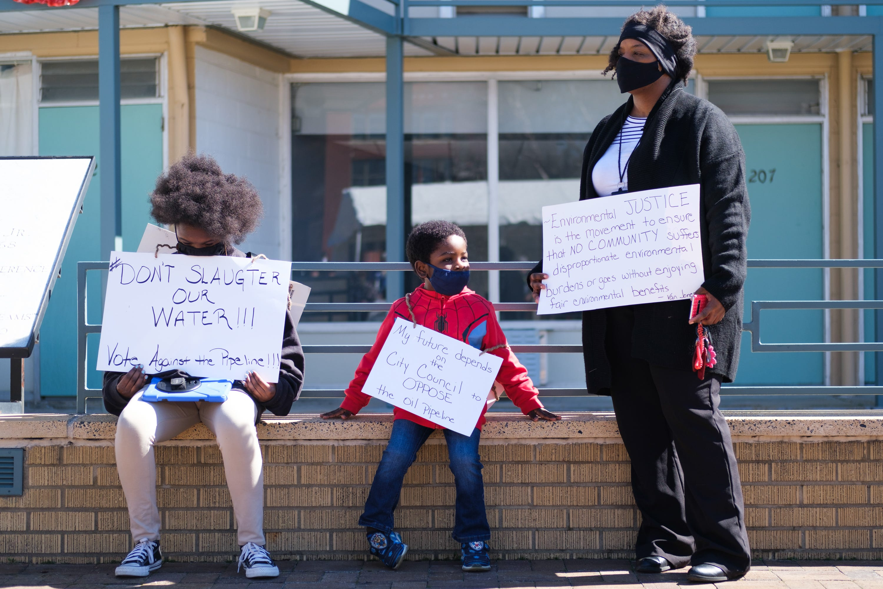 Kizzy Jones, a co-founder of Memphis Community Against the Pipeline (MCAP), hold signs outside the National Civil Rights Museum with her family during a rally against the construction of the Byhalia Connection Pipeline, Tuesday, Feb. 23, 2021, in Memphis, Tenn.