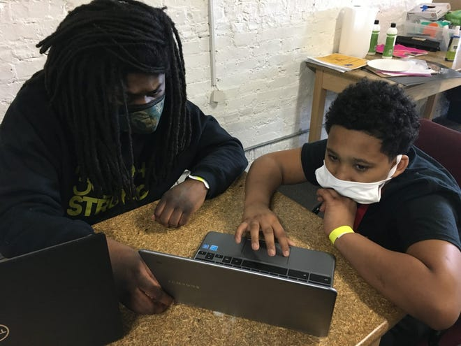 Forrest Jackson, education coordinator at Running Rebels community organization, helps a child with his virtual school work.
