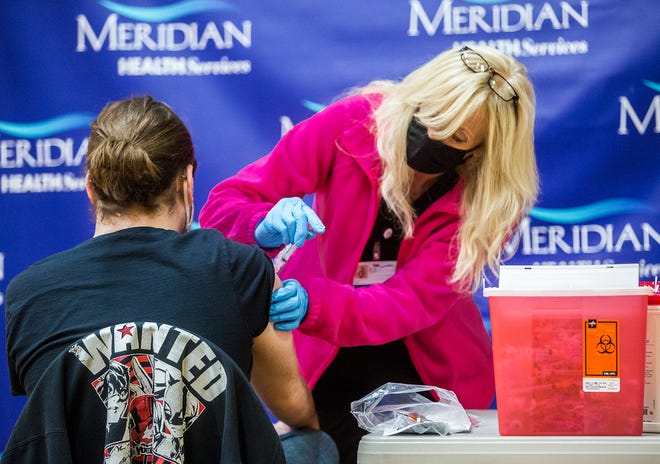 A person receives the Moderna COVID-19 vaccination at the Suzanne Gresham Center through Meridian Health Services.