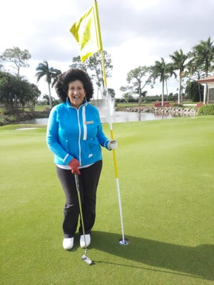 Wendy Nickerson poses after making a hole-in-one with a putter, holding the flag with her hole-in-one ball in the cup at The Glades Golf & Country Club in Naples, Florida, on Feb. 2, 2021.