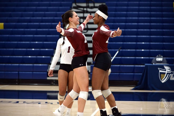 Savannah Davison (left) and Victoria Barrett (right) celebrate after earning a point during New Mexico State's match against Cal Baptist on Feb. 23, 2021, in Riverside, California.