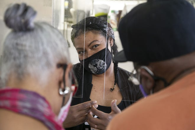 Krystal Harris, center, owner of the Early Bird Vegan, takes an order through a plexiglass partition from customers Arline Simmons, left, and her husband, Paul Simmons, at the vegan cafe in Phoenix on Feb. 23, 2021. The partition is for safety because of COVID-19 concerns.
