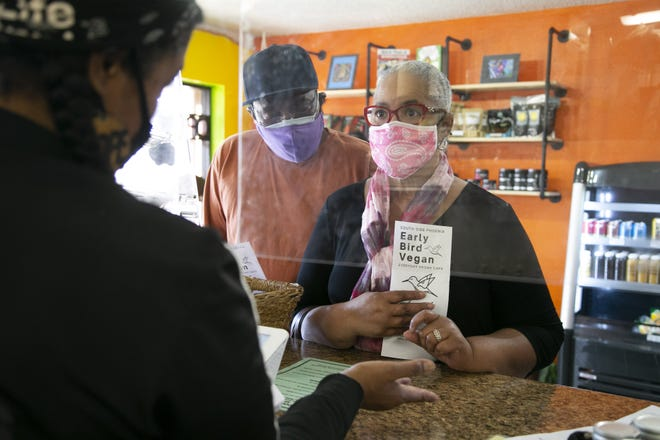 Krystal Harris, left, owner of the Early Bird Vegan, takes an order through a plexiglass partition from customers Arline Simmons and her husband, Paul Simmons, at the vegan cafe in Phoenix on Feb. 23, 2021. The partition is for safety because of COVID-19 concerns.