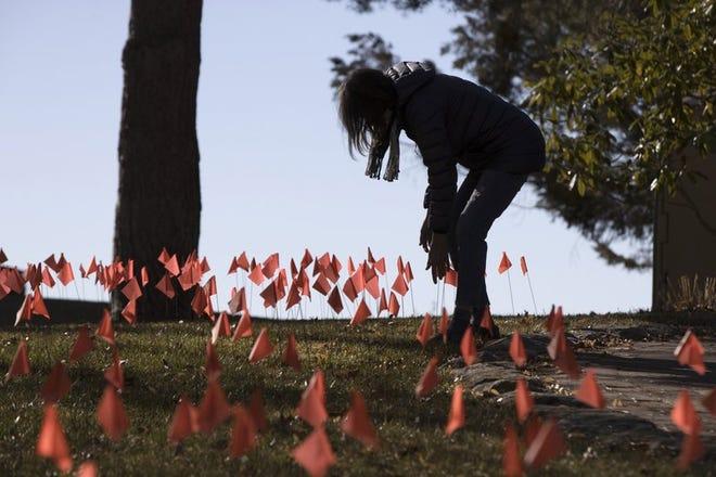 Cindy Pollock revisa las banderas que colocó en su jardín, el miércoles 10 de febrero de 2021, en Boise, Idaho.