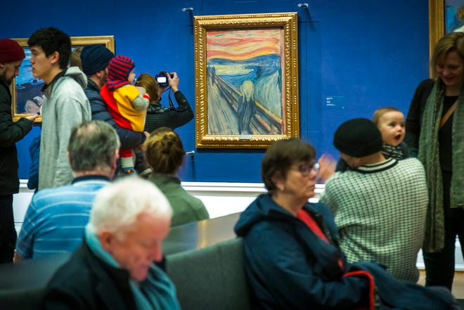 """FILE - In this Sunday, Jan. 13, 2019 file photo, people look at """"The Scream"""" at the National Gallery in Oslo. A Norwegian museum says a small, barely visible sentence written on Edvard Munch's 1893 masterpiece """"The Scream"""" was penned by the Norwegian painter himself. The sentence referring to the artwork being made by a madman was scribbled in a corner. A curator at the new National Museum of Norway said Monday, Feb. 22, 2021 the inscription was likely made in 1895, when Munch exhibited the painting for the first time and was met with questions about his mental health. (Heiko Junge/NTB Scanpix via AP, file)"""