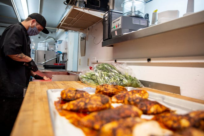 Nathan Trimmer preps chicken as Gamberetti's Italian Restaurant on Tuesday as the restaurant works to return to indoor dining.