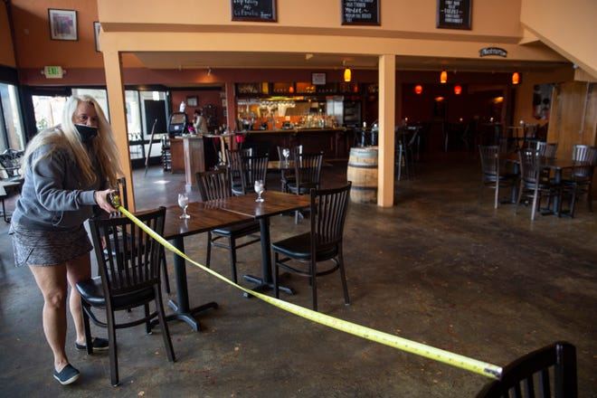 Treva Gambs measures the distance between tables at Gamberetti's Italian Restaurant as they prepare to return to indoor dining.
