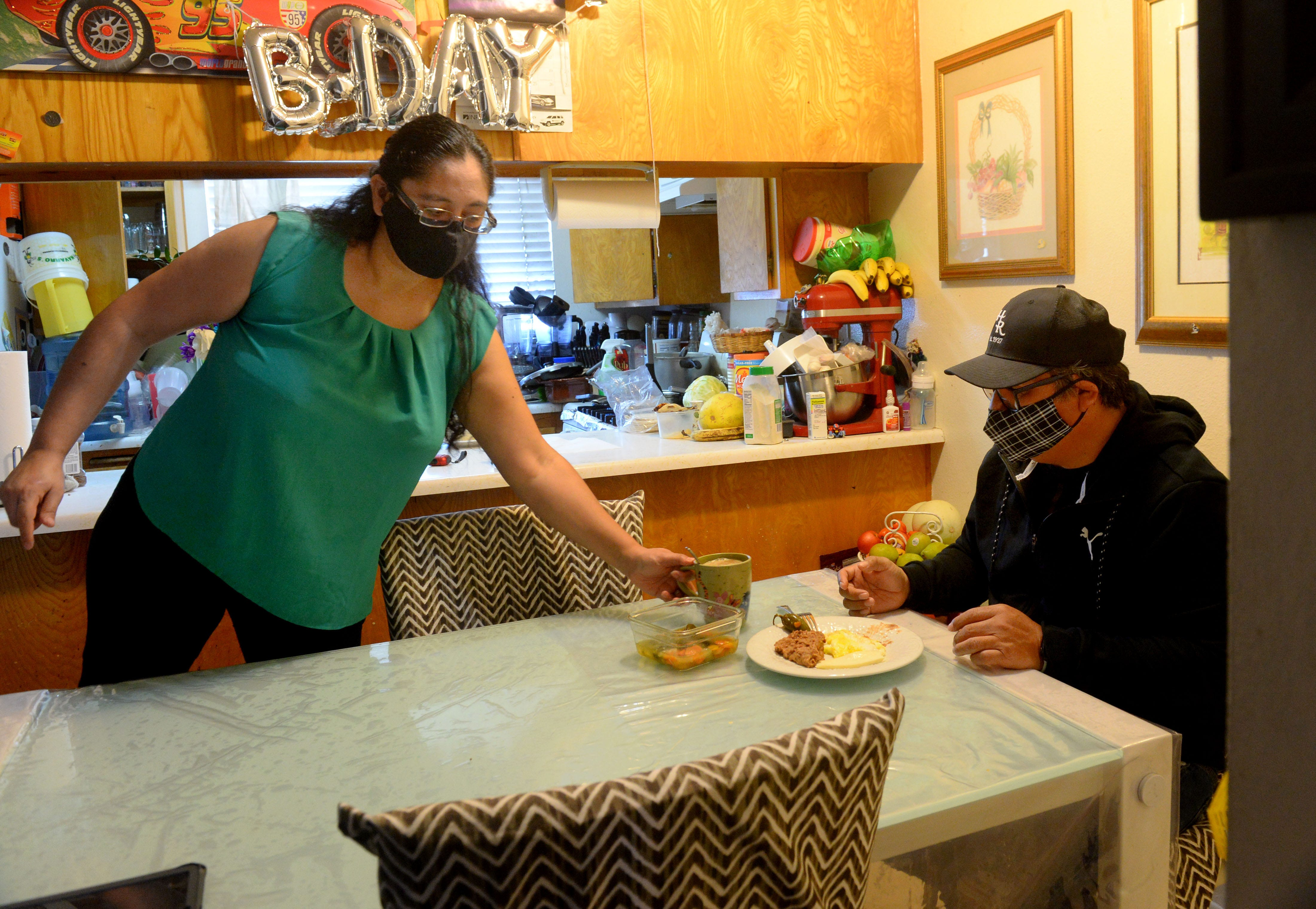 Jessica Vargas, left, brings breakfast to her husband Jorge Ruiz on Monday, Feb. 22, 2021. They have two children and are heavily involved in their education.