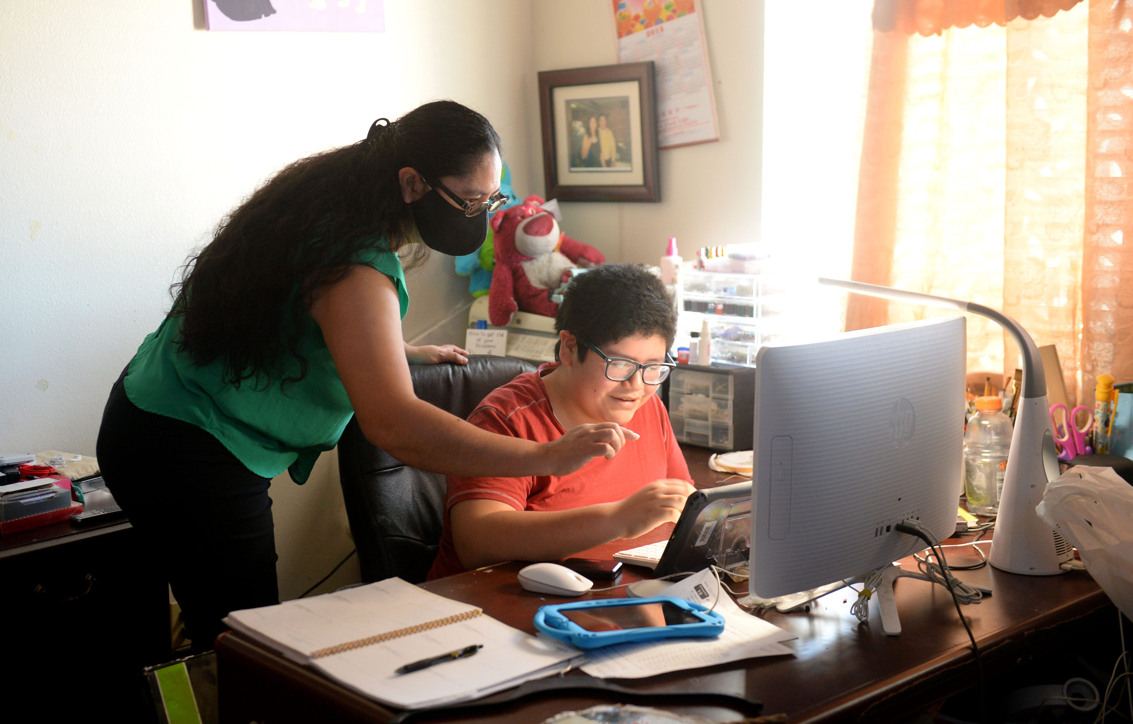 Jessica Vargas, left, helps her son Jorge Alberto Ruiz, 13, with his online classes on Monday, Feb. 22, 2021. Jorge is enrolled in special education classes and needs daily help from his mom.