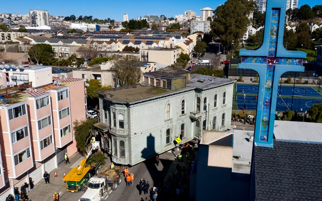 A truck pulls a Victorian home through San Francisco on Sunday, Feb. 21, 2021.