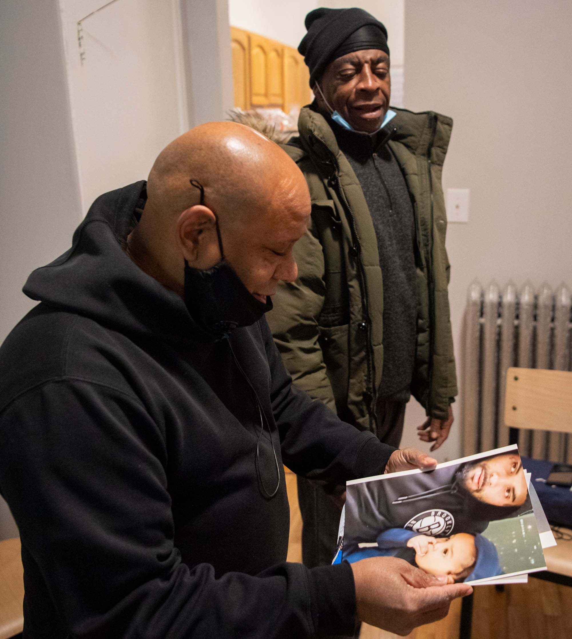 Shams DaBaron (left) and Larry Thomas (right) look at photos of Thomas' family in his new home in West Harlem on Dec. 6, 2020.