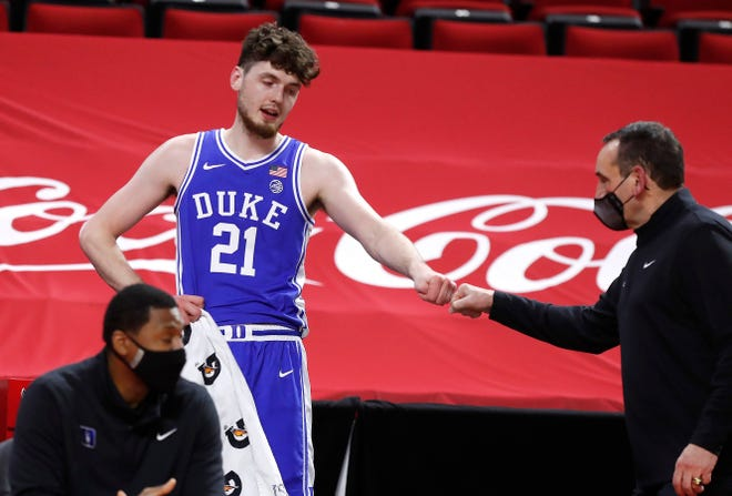 Duke's Matthew Hurt (21) fist bumps head coach Mike Krzyzewski during the second half of an NCAA college basketball game against North Carolina State at PNC Arena in Raleigh, N.C.