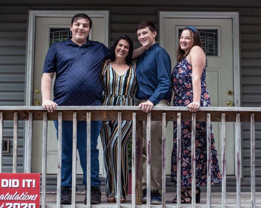 Misty Mcdade and her three children pose for a photo outside their home to celebrate her son's school graduation in Morgantown, W. Va. The single mom of three had to move from their townhouse out to a trailer after being laid off from her accounting job as a result of COVID-19.