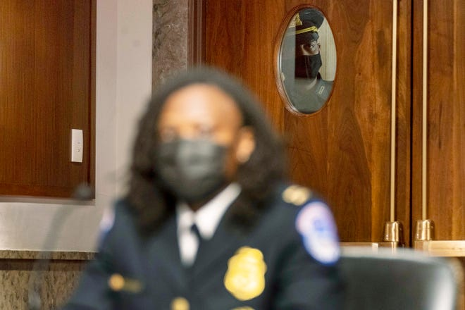 An officer looks through a window as Capitol Police Capt. Carneysha Mendoza, foreground, prepares to speak at a Senate Homeland Security and Governmental Affairs & Senate Rules and Administration joint hearing on Capitol Hill, Washington, Tuesday, Feb. 23, 2021, to examine the January 6th attack on the Capitol.