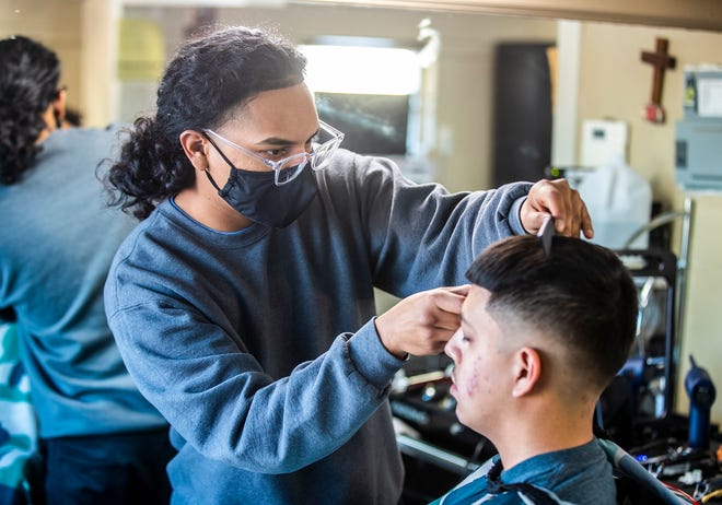 Round Rock barber Gabriel Escobedo, who works for EscoFades, cuts Jeremiah Ortega's hair on Monday. Escobedo was offering free haircuts to H-E-B employees to show appreciation for their work during the winter storm.