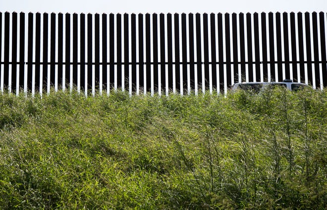A Border Patrol vehicle guards a section of border fence on in Runn, east of McAllen in South Texas, in 2017. A federal court in Texas suspended a 100-day moratorium on deportations enacted by President Joe Biden, who rushed to send the most ambitious overhaul of the nation's immigration system in a generation to Congress and signed nine executive actions to wipe out some of his predecessor's toughest measures to fortify the U.S.-Mexico border.