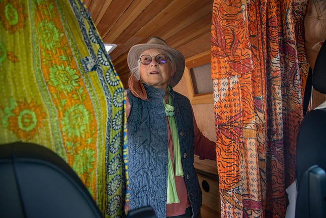 Dolores Kuykendall fixes the curtains in her Sprinter van in South Austin on Wednesday after securing a coronavirus vaccine appointment through Austin Public Health. Kuykendall plans to return to traveling in her van after her two vaccination appointments are complete.
