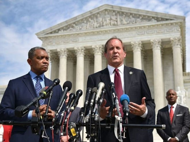 Texas Attorney General Ken Paxton -- flanked by District of Columbia Attorney General Karl Racine -- leads a news conference outside the Supreme Court building in Washington, D.C., in 2019 announcing an antitrust investigation into Google. [The New York Times]