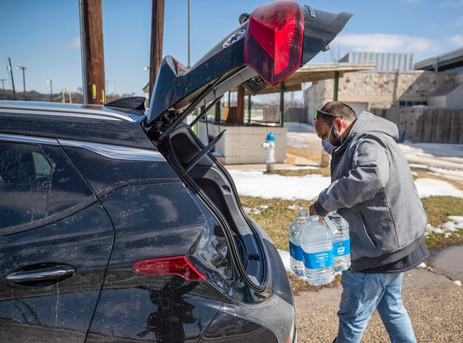 Martin Lopez loads up his car with water after refilling the bottles at Georgetown Community Center on Feb.19. Williamson County commissioners on Tuesdayapproved an extra $300,000 in spending to cover the cost of responding to last week's winter storm, including efforts to get water to residents with no potable source and no service at all.