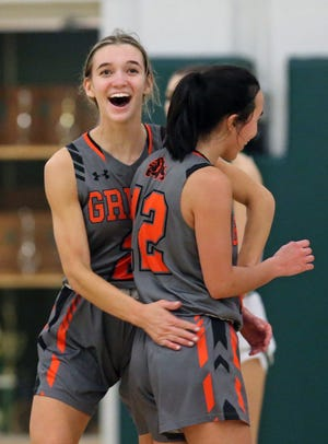 Green's Olivia Payne, facing, congratulates Bri Hunt after she made a 3-pointer during the Bulldogs' 45-44 win over Nordonia in a Division I district semifinal Tuesday night in Macedonia. [Jeff Lange/Beacon Journal]