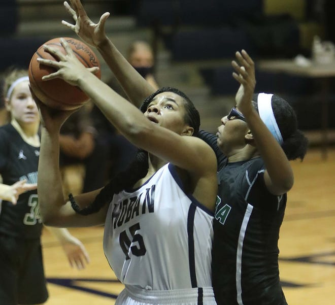 Lanae Riley, left, of Archbishop Hoban goes up for two points as a foul is called on Shyanne Sellers of Aurora during the first half of their Division I district semifinal game Tuesday night in Akron. Hoban won 74-56. [Karen Schiely/Beacon Journal]
