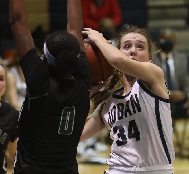 Archbishop Hoban's Grace Schill drives to the basket during a district tournament game. [Karen Schiely/Beacon Journal]
