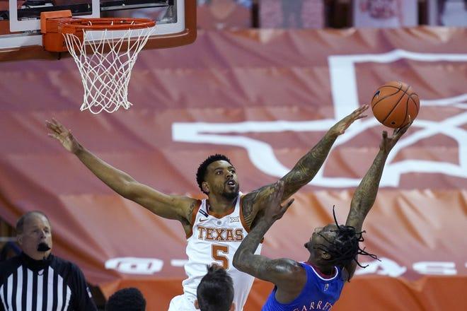 Texas forward Royce Hamm Jr. (5) tries to block a shot by Kansas guard Marcus Garrett, right, during the first half of an NCAA college basketball game, Tuesday, Feb. 23, 2021, in Austin, Texas.