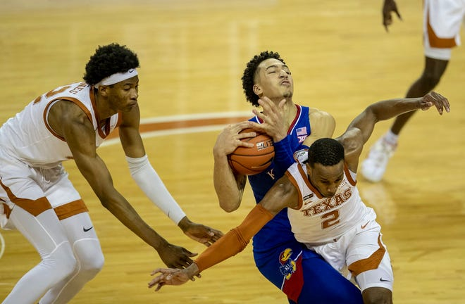 Texas guard Matt Coleman III, right, fouls Kansas forward Jalen Wilson during overtime of the Longhorns' 75-72 win on Tuesday night. Texas swept the Jayhawks in their regular-season series for the first time ever as Big 12 programs.