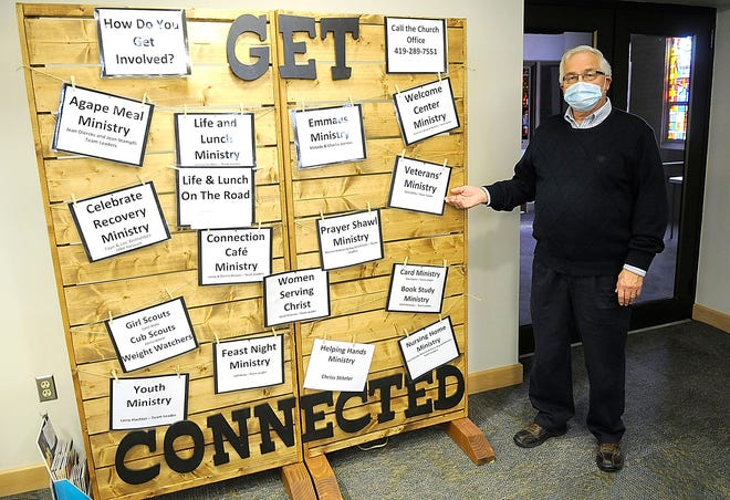 """Jack Cadley points out the Veterans' Ministry sign on the """"Get Connected"""" board at First United Methodist Church. TOM E. PUSKAR/TIMES-GAZETTE.COM"""
