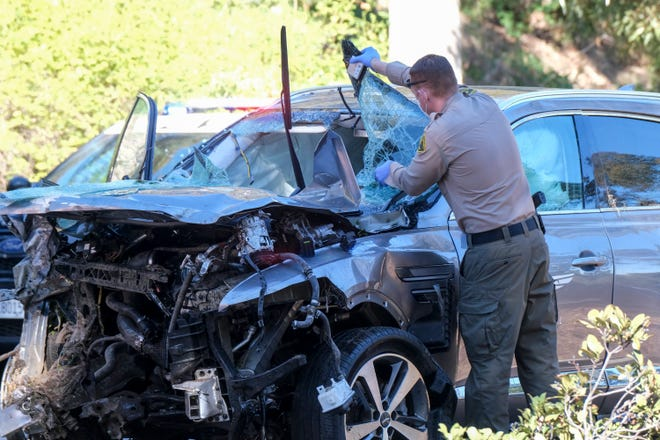 A law enforcement officer checks the damaged vehicle Tiger Woods was driving when the golfer crashed in a Los Angeles suburb on Tuesday.