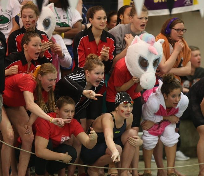 Swimmers, and a couple of Unicorn mascots, from Columbus School for Girls crowd onto the deck to cheer on a teammate during a race in the 2018 state meet in Canton's C.T. Branin Auditorium. Social distancing won't allow for such close quarters this year.