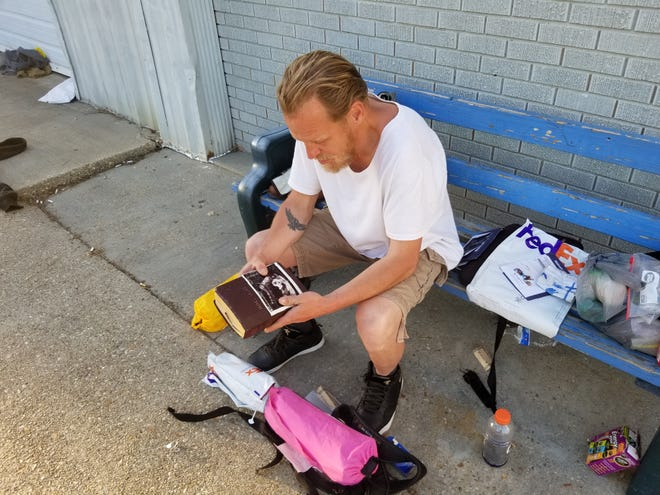 William Byrne gathers his things outside the House of Hope shelter in Houma.