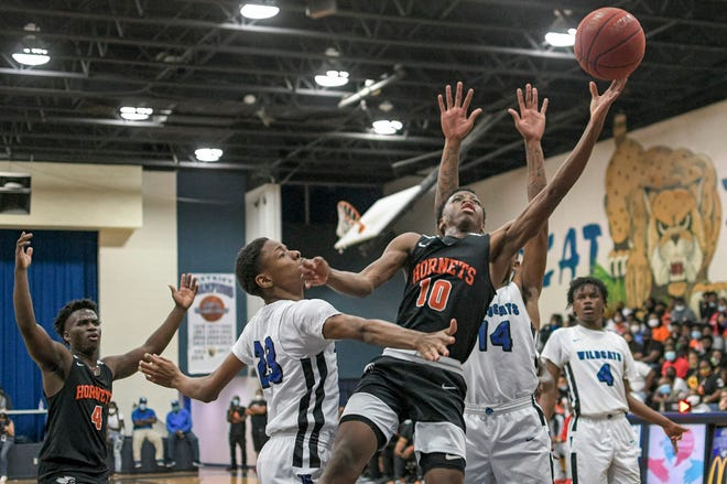 Hawthorne's CJ Ingram (10) reaches for a rebound during Tuesday's Class 1A-Region 4 championship game against Wildwood in Wildwood. [PAUL RYAN / CORRESPONDENT]