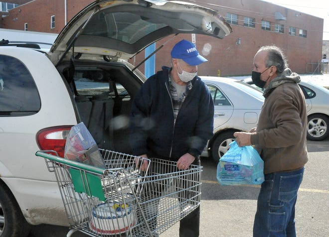 Joe Smith (left) helps put food in Jake Hershberger's van. Hershberger values the work of the Wooster Hope Center for his family. He previously served as a volunteer at a local food bank.
