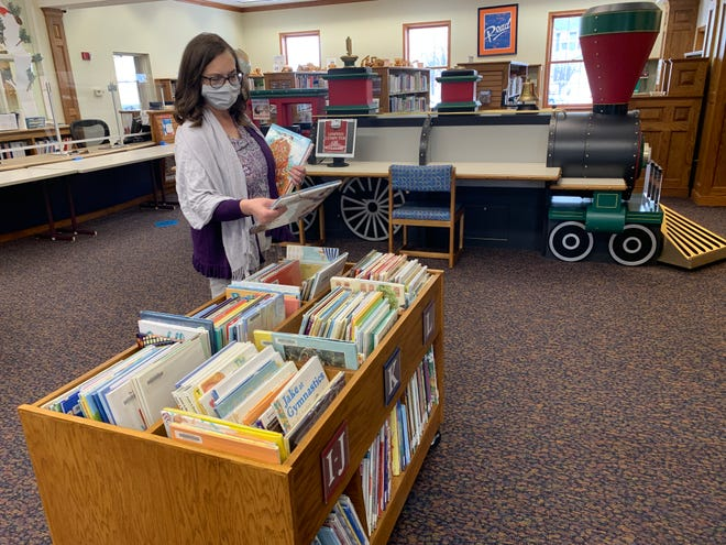 Tammy Daubner, manager of youth services at Orrville Public Library, picks out books in the children's section. She has enjoyed curating a collection of books for families who don't want to come into the library during the pandemic and will instead pick up the items.