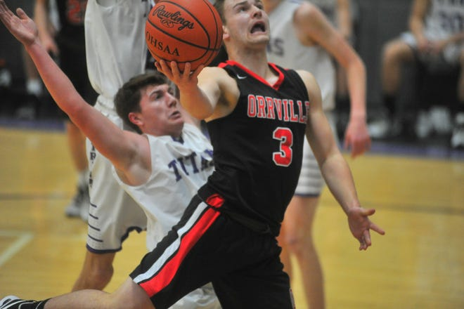 Orrville's Cooper Haley gets to the basket in front of Triway's Zack Miller. Haley scored 17 for the Red Riders.