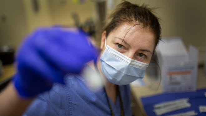 Infectious Disease Pharmacist Zina Gugkaeva inspects a a vile that contains Pfizer COVID-19 vaccine inside Maury Regional Medical Plaza in Columbia, Tenn., on Wednesday, Feb. 24, 2021.