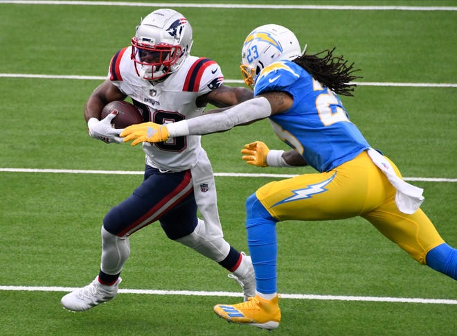 Dec 6, 2020; Inglewood, California, USA; New England Patriots running back James White (28) tries to break free from  Los Angeles Chargers free safety Nasir Adderley (24) during the second quarter at SoFi Stadium.