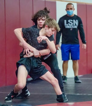 Lee's Summit North freshman wrestler Charlie Dykes, front, works on drills with teammate Owen Barnhill during a recent practice. Dykes, despite being born with a clubfoot on his left leg, has developed into a 113-pound district champion this season and enters Saturday's sectional tournament as a No. 1 seed.